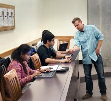 An instructor assists graduate students during a graphic design workshop