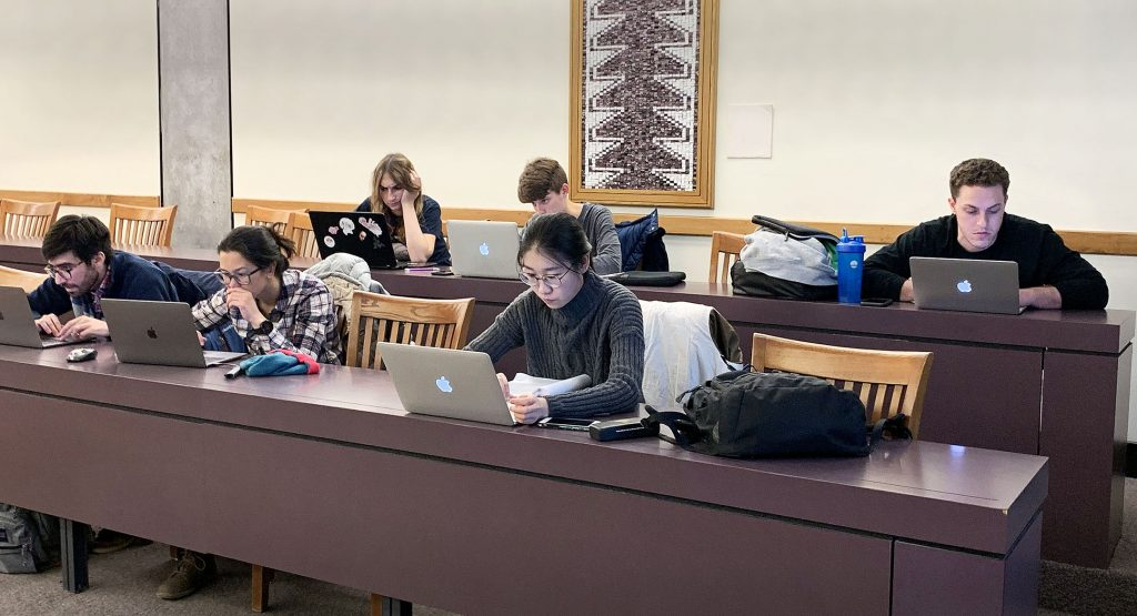 Graduate students work on their computers during a graphic design workshop