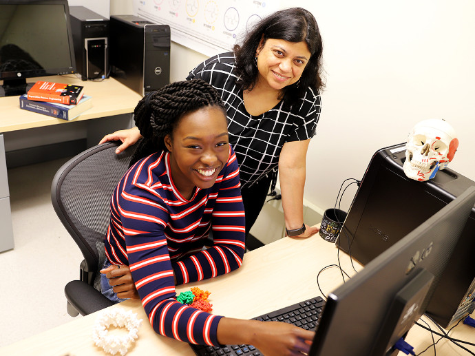Professor Nangia and one of her students working on a computer.